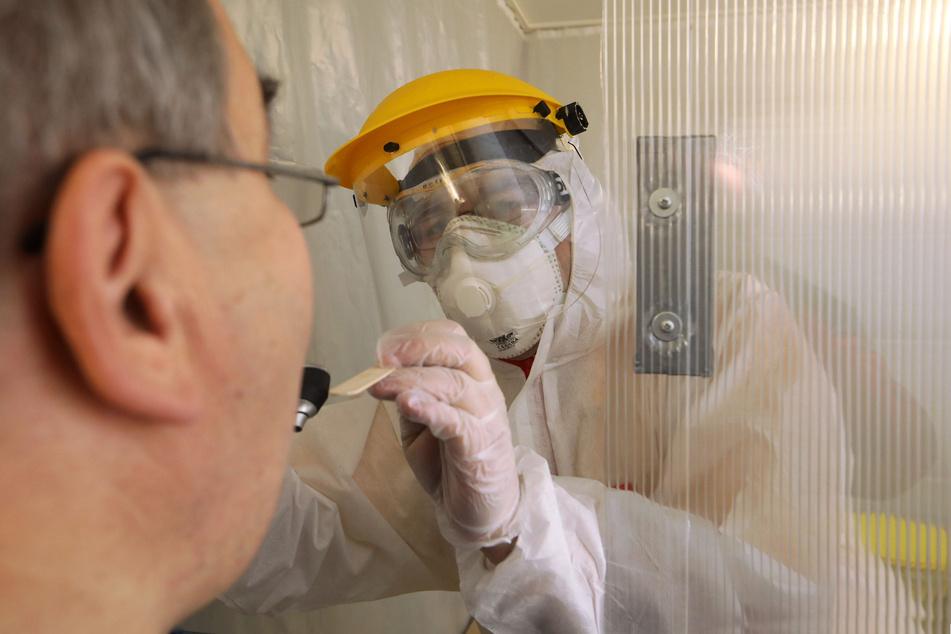 Christoph Lohmann (34) behandelt einen Patienten in der Fieberambulanz. Er trägt Vollschutz und FFP3-Maske.