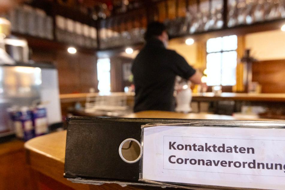 """Ein Ordner mit der Aufschrift """"Kontaktdaten Coronaverordnung"""" liegt in einer Gaststätte auf der Theke."""