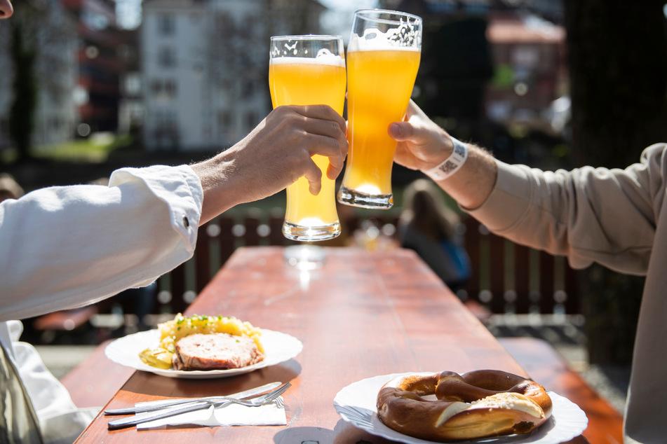 Zwei Menschen sitzen bei gutem Wetter in einem Biergarten. Bei stabilen Inzidenzwerten unter 100 sollen in Thüringen unter anderem Biergärten wieder öffnen dürfen.