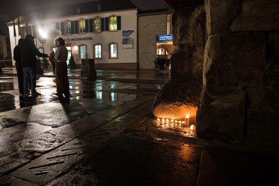 Mit Einbruch der Dunkelheit stellen Menschen in Trier Kerzen auf. An der Porta Nigra flackern kleine Teelichter.