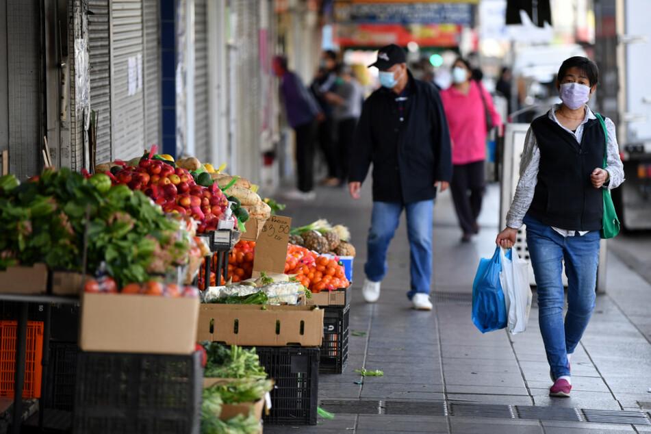 Kunden mit Gesichtsmasken gehen die Beamish Street in Campsie in Sydney entlang.