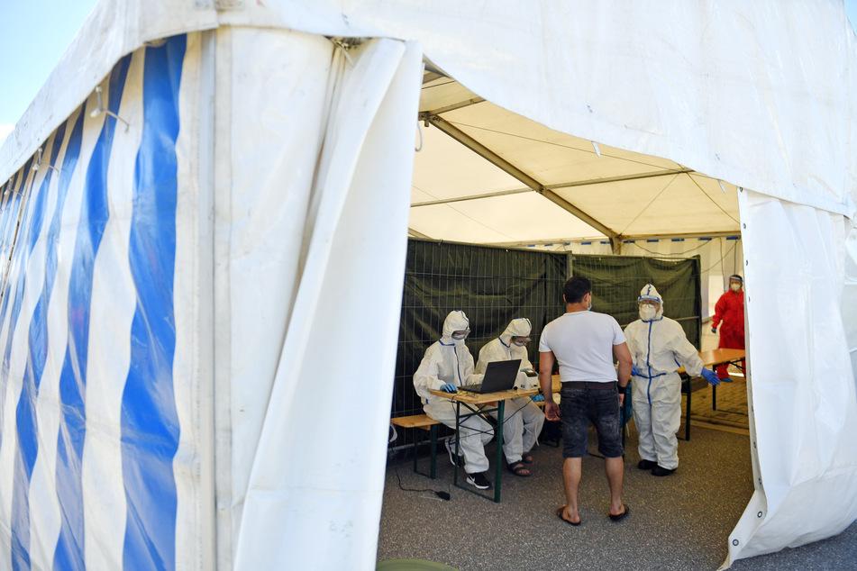 Ein Mitarbeiter (M) des Schlachthofes von Tönnies in Weißenfels stellt sich in einem Zelt neben dem Schlachthofgelände zum Corona-Test vor.