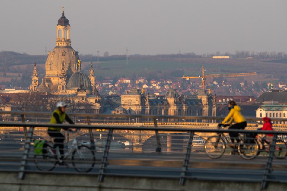 Wenige Radler sind vor der Kulisse der Stadt Dresden unterwegs.