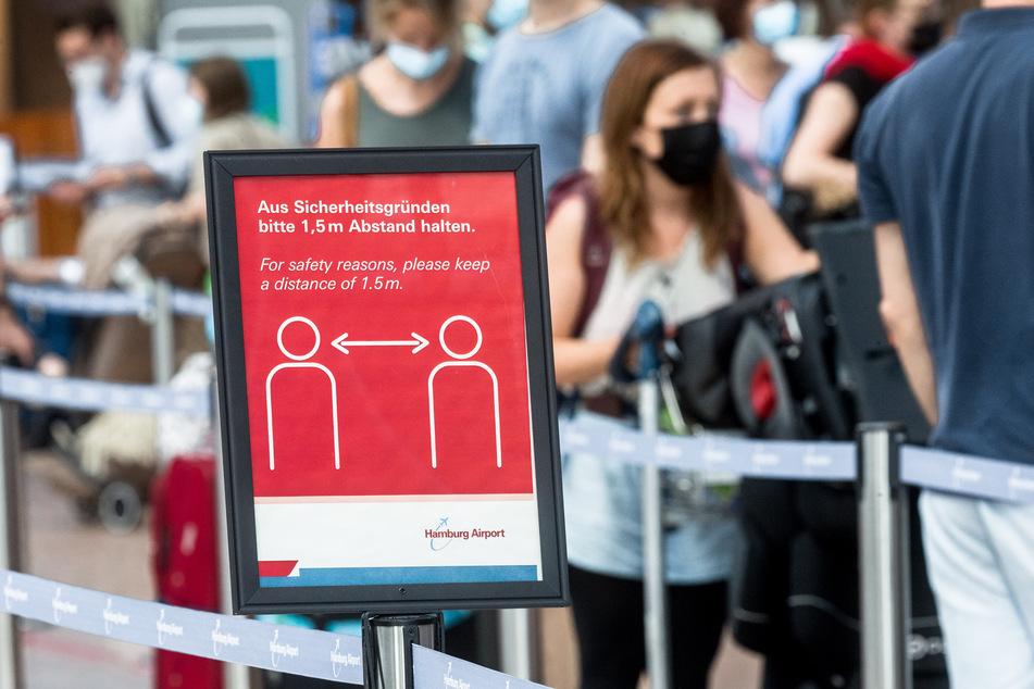 Reisende stehen in einer Warteschlange am Hamburger Flughafen.