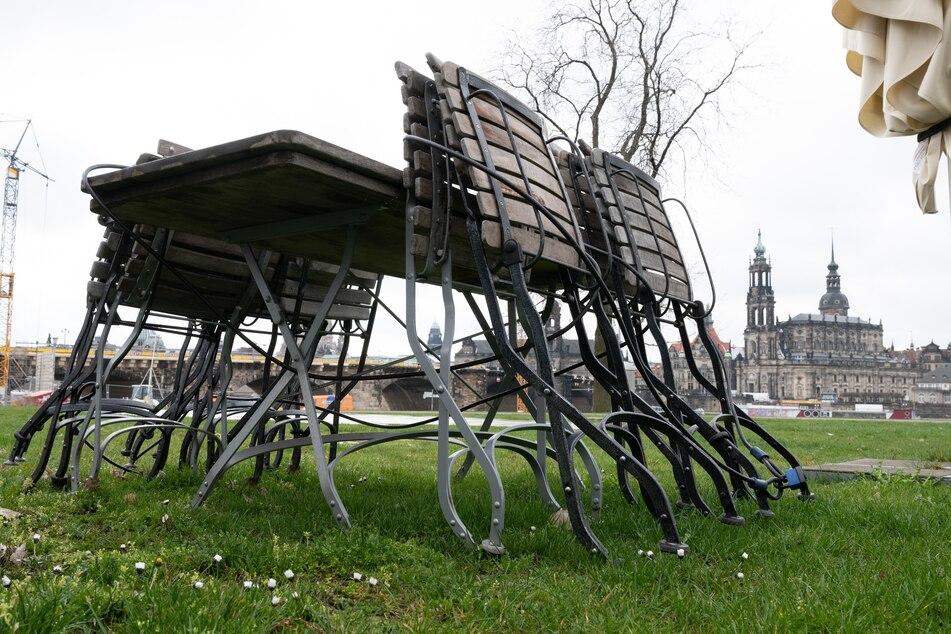 Tische und Stühle stehen vor der Kulisse der Altstadt mit der Katholischen Hofkirche an einem geschlossenen Restaurant.