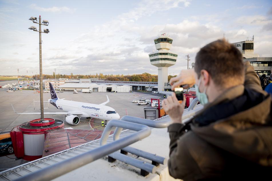 """Ein Mann fotografiert am Flughafen Berlin-Tegel einen Airbus der Lufthansa mit der Aufschrift """"Hauptstadtflieger""""."""