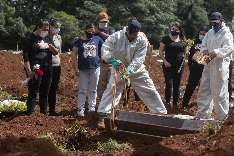 Menschen nehmen an der Beerdigung eines Verwandten auf dem Friedhof Vila Formosa in Sao Paolo teil, der an Komplikationen im Zusammenhang mit einer Covid-19-Infektion gestorben ist.