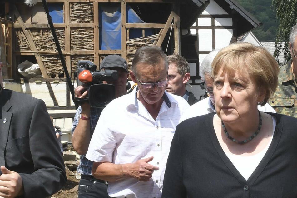 Bundeskanzlerin Angela Merkel (3.v.r.) und Malu Dreyer (2.v.r,SPD), Ministerpräsidentin von Rheinland-Pfalz, gehen durch das vom Hochwasser verwüstete Dorf Schuld in der Nähe von Bad Neuenahr-Ahrweiler.