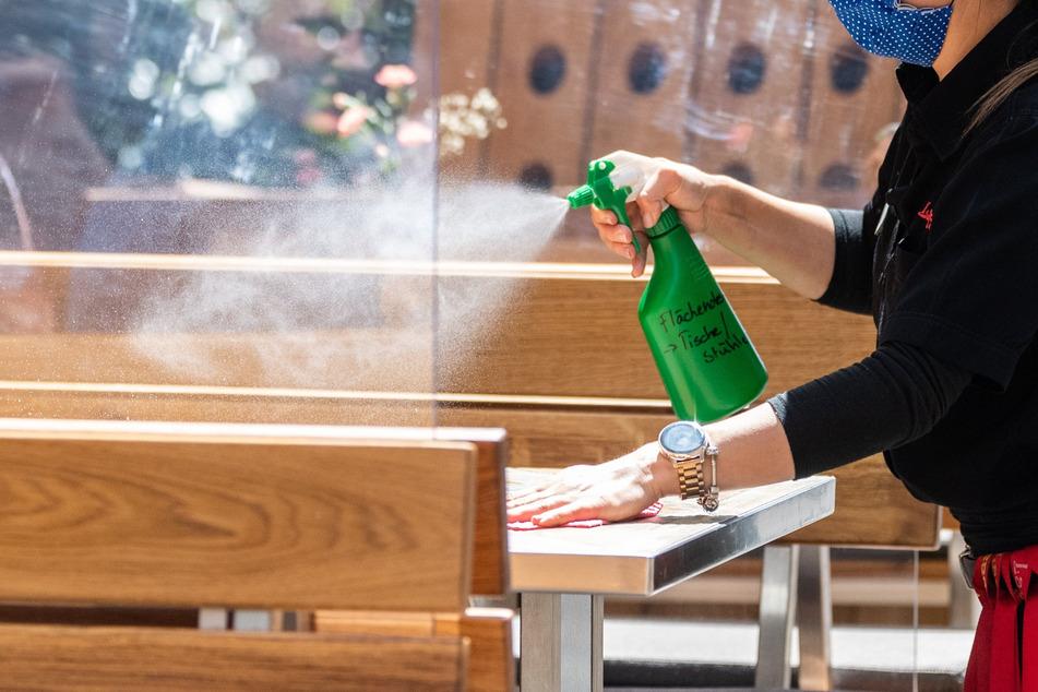 Eine Mitarbeiterin eines Restaurants in Dresden reinigt die Tische mit Desinfektionsmittel.