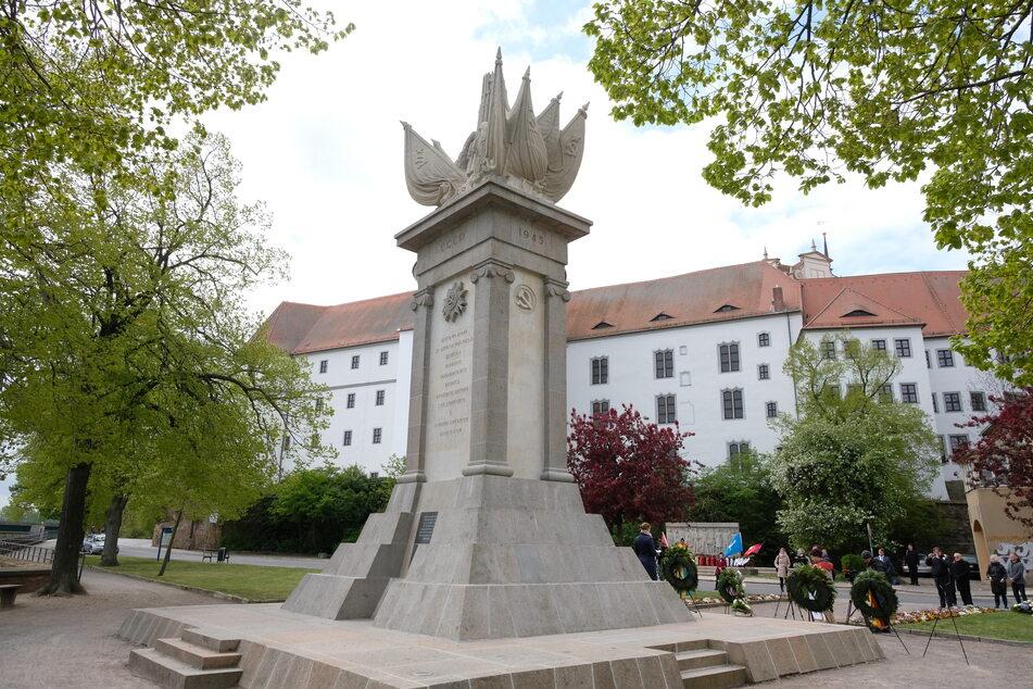 Das Denkmal der Begegnung mit Schloss Hartenfels im Hintergrund.