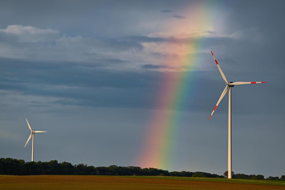 """Ein Regenbogen spannt sich über die Landschaft mit zwei Windenergieanlagen im Windpark """"Odervorland"""" im Landkreis Oder-Spree."""