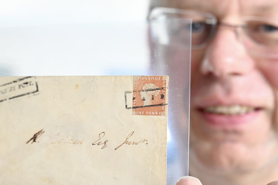 Christoph Gärtner, der Geschäftsführer des Auktionshauses Christoph Gärtner, hält bei der Pressekonferenz zur Versteigerung eines Briefumschlags mit der Briefmarke Rote Mauritius den Umschlag mit der Marke in der Hand.