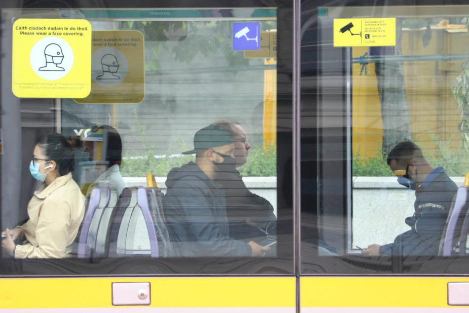 Irland, Dublin: Fahrgäste mit Gesichtsmasken fahren in einer Straßenbahn.