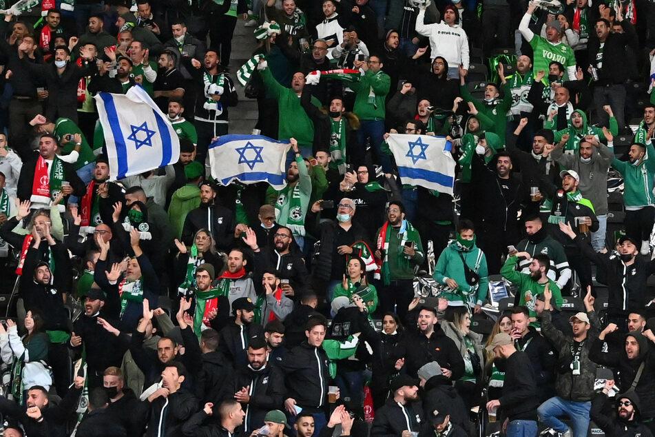 Haifa-Fans zeigen auf der Tribüne israelische Flaggen, im Stadion soll es zu antisemitischen Beleidigungen gekommen sein.