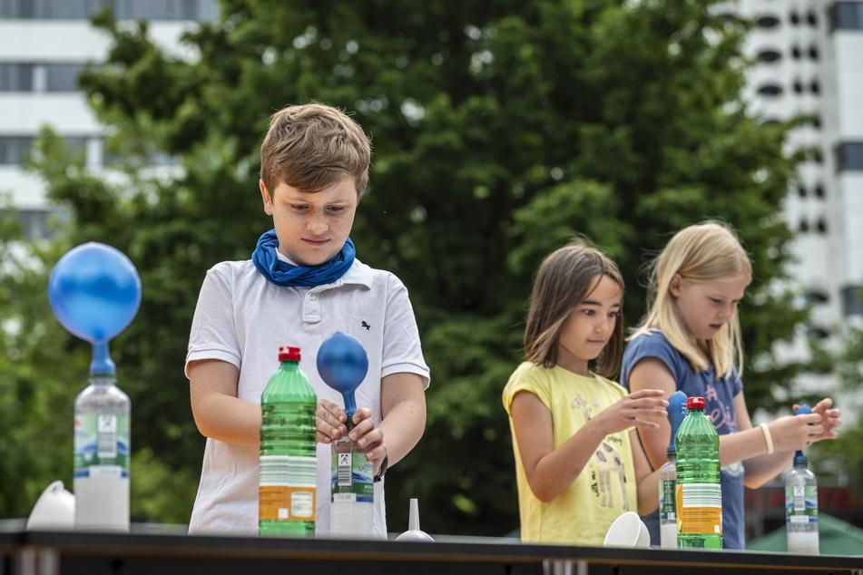 Kinder füllten bei der Mitmach-Vorlesung von Shary Reeves eine Flasche mit Backpulver und Essig und pusteten so einen Luftballon auf.