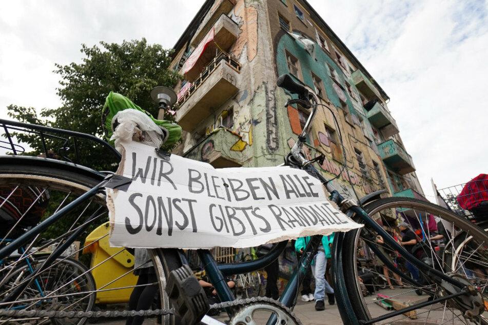 """Ein Pappkarton mit der Aufschrift """"Wir bleiben Alle, sonst gibts Randale"""" ist bei der Fahrrad-Demonstration auf einem Fahrrad befestigt, das vor dem Gebäude Liebigstraße 34 steht."""