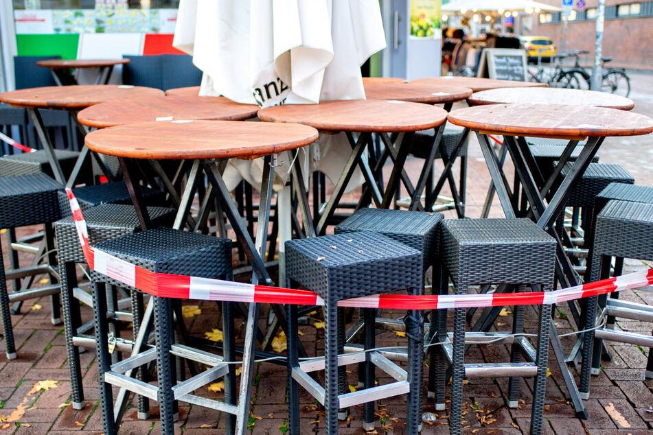 Tische und Stühle stehen vor einer Pizzeria, die derzeit nur Speisen zum Mitnehmen anbieten kann.