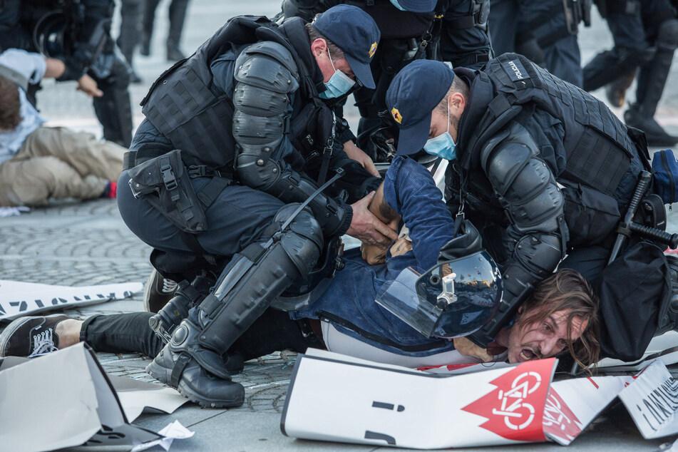 Zwei Polizisten mit Mundschutz verhaften einen Demonstrant am Rande eines Protestes gegen die Regierung. Jeden Freitag protestieren in Ljubljana Menschen gegen die Regierung von Premierminister Jansa, der sie Korruption vorwerfen.