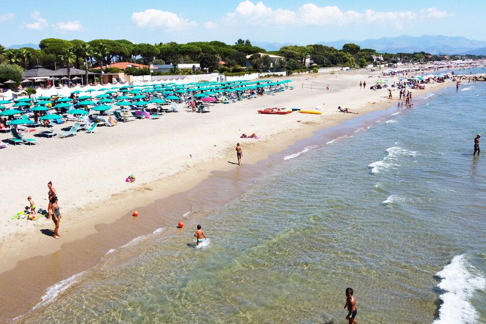 Einige Besucher baden im Meer am italienischen Strand.