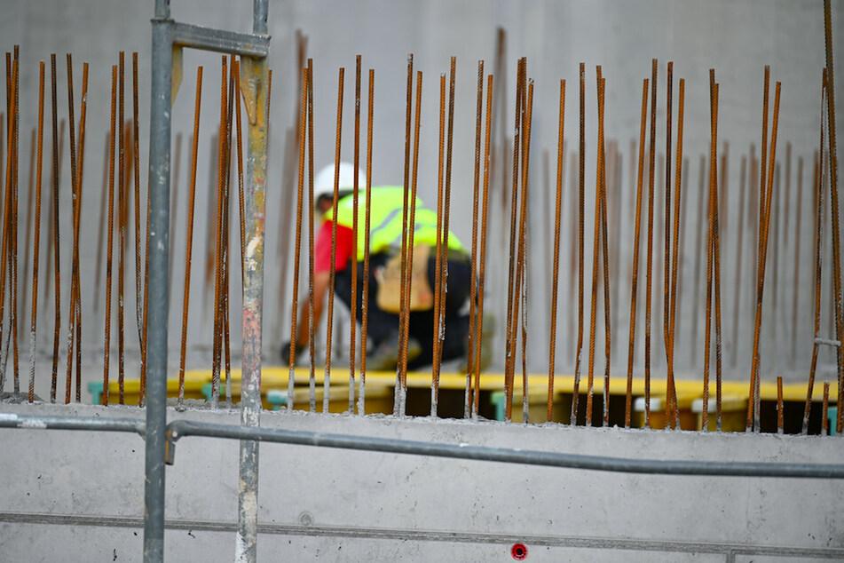 Ein Handwerker arbeitet auf einer Baustelle an Betonstahlträgern. (Symbolbild)