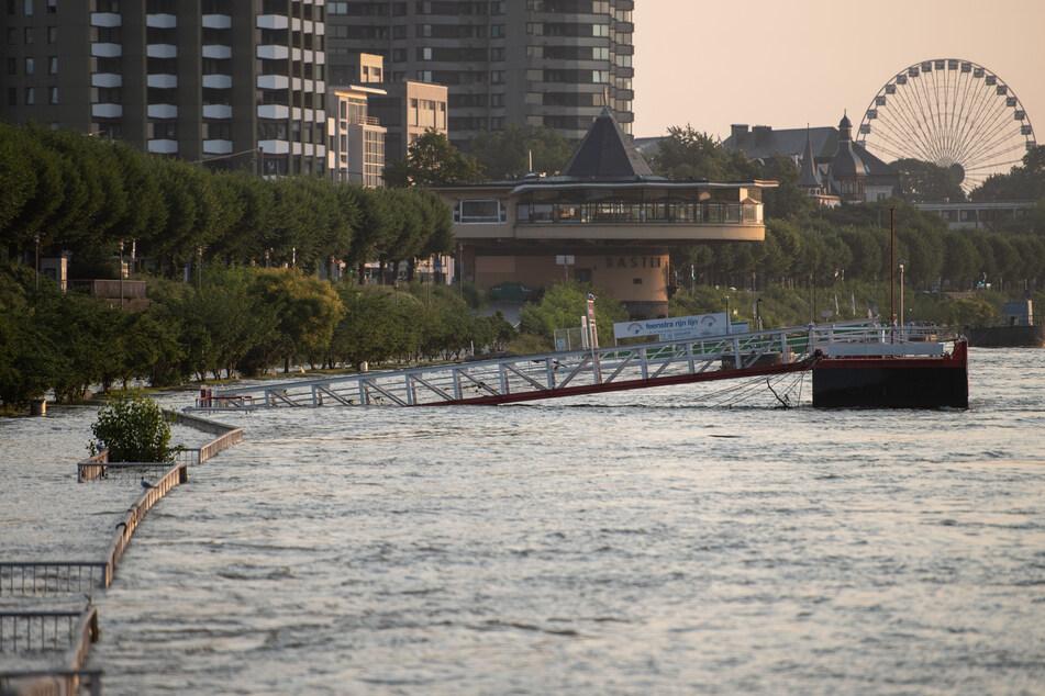 Nach dem Unwetter: In Köln sind Bootsanleger und ein Weg vom Rhein überflutet. Die nächsten Tage soll es in Nordrhein-Westfalen meist trocken bleiben.