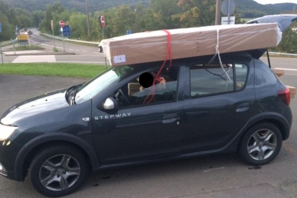 Fahrer und Beifahrer mussten die Matratze auf dem Dach während der Fahrt festhalten.