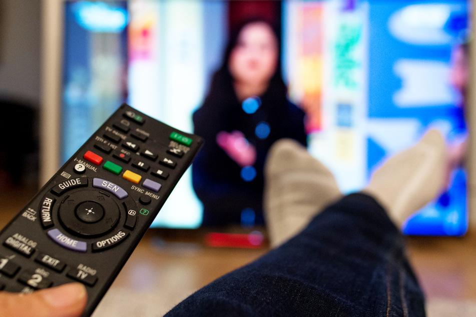 Eine Frau sitzt vor einem Fernseher und hält eine Fernbedienung in der Hand. (Symbolbild)