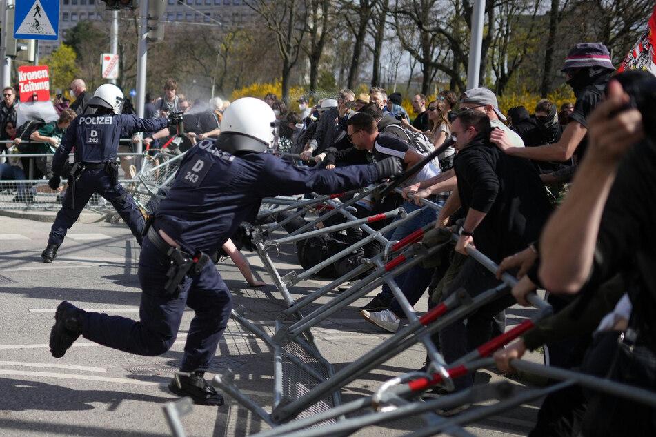 Wien: Demonstranten versuchen Straßenabsperrungen zu durchbrechen, hinter der zwei Polizisten stehen.