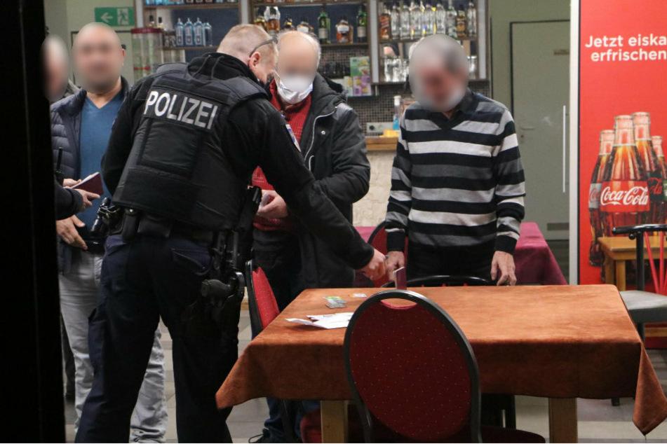 Ein Polizist diskutiert mit dem Café-Betreiber, der seine Maske noch immer nicht ordnungsgemäß trägt. Ein anderer Gast hat seinen Mund-Nasen-Schutz mittlerweile angelegt, ein Dritter verzichtet jedoch weiterhin vollständig darauf.