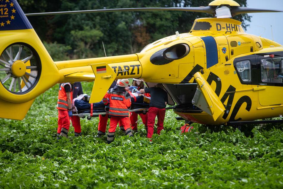 Rettungskräfte verladen eine verletze Person in einen Rettungshubschrauber.