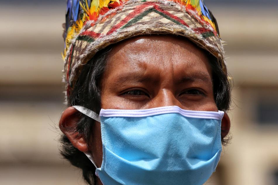 Kolumbien, Bogotá: Ein Mitglied eines indigenen Volkes trägt während einer Demonstration in Bogota eine Maske zum Schutz vor dem Coronavirus.