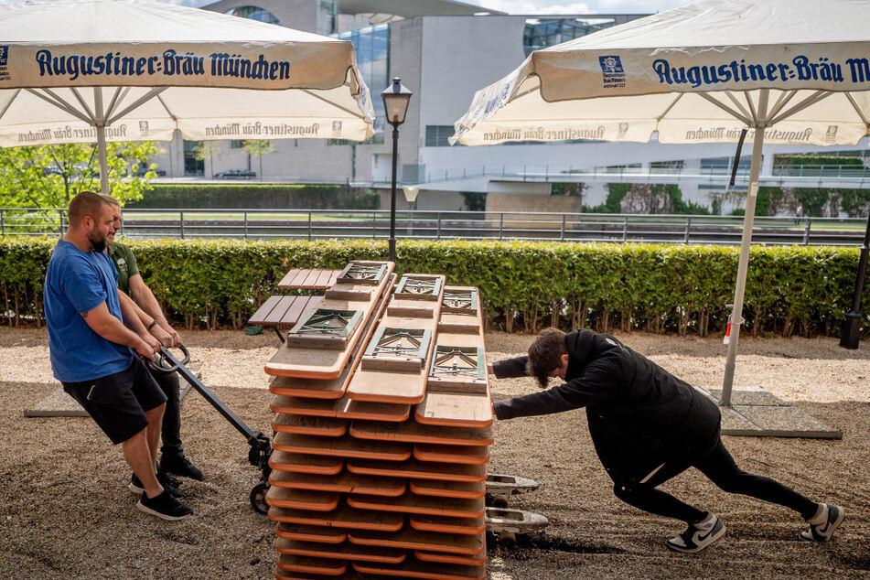 Mitarbeiter des Zollpackhofs ziehen Bierbänke über den Kies und bereiten gegenüber des Bundeskanzleramts den Biergarten für die Öffnung nach dem Lockdown am 21.05.2021 vor.