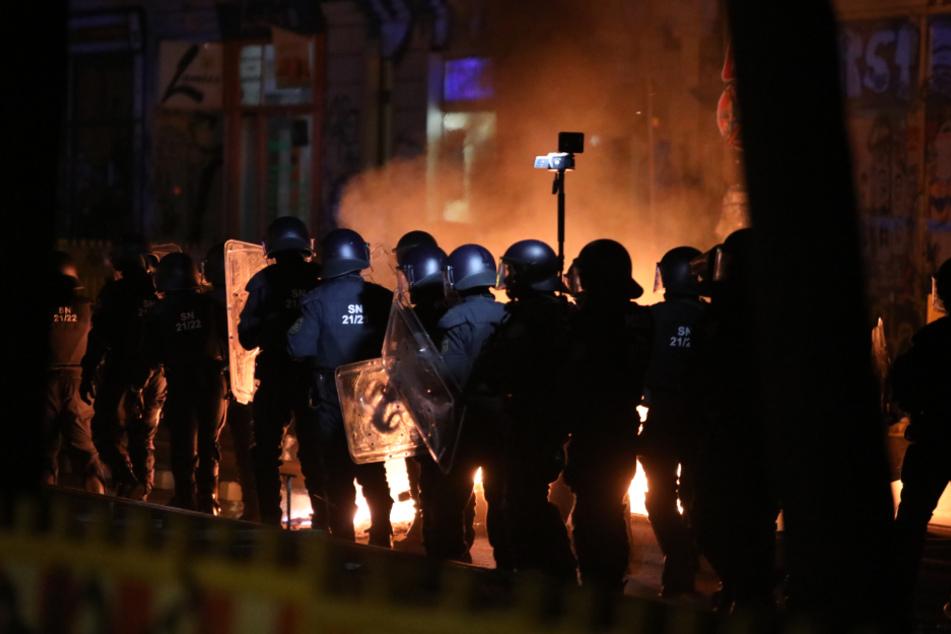 Bereitschaftspolizisten sichern die Löscharbeiten ab - und werden dabei mit Steinen und Flaschen beworfen.