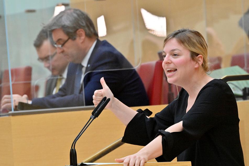 Katharina Schulze (35), Fraktionsvorsitzende Bündnis 90/Die Grünen im bayerischen Landtag, spricht in der Sondersitzung des Landtags zur Corona-Krise. Im Hintergrund ist Ministerpräsident Markus Söder zu sehen.