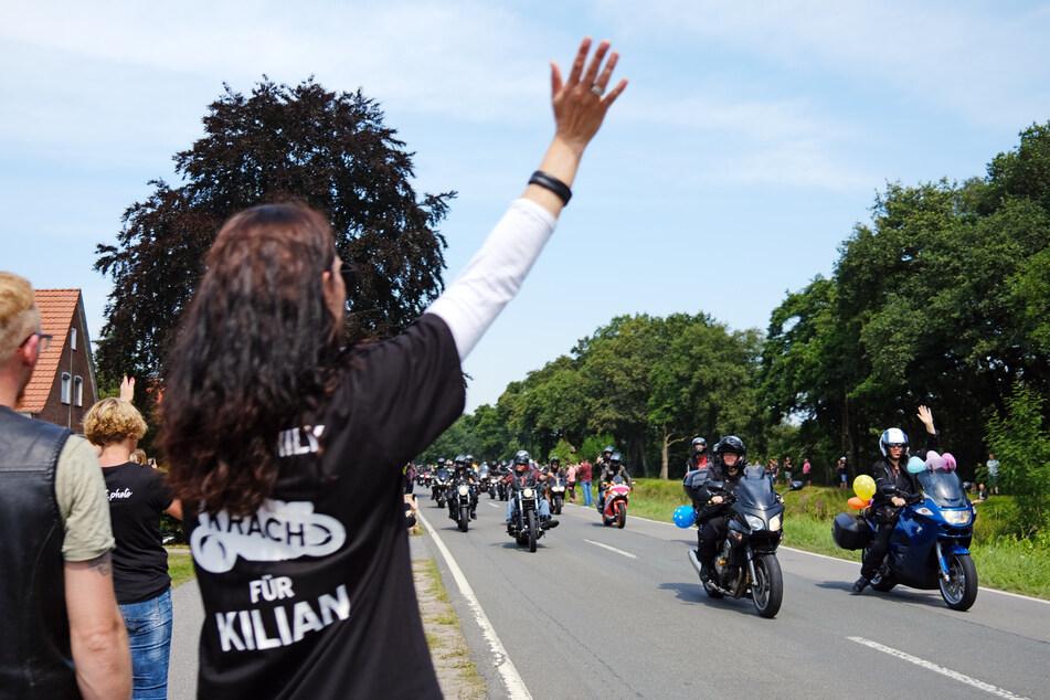 """Eine Frau mit einem T-Shirt mit der Aufschrift """"Krach für Kilian"""" winkt den Motorradfahrern, die am Haus des krebskranken Kilian vorbeifahren."""