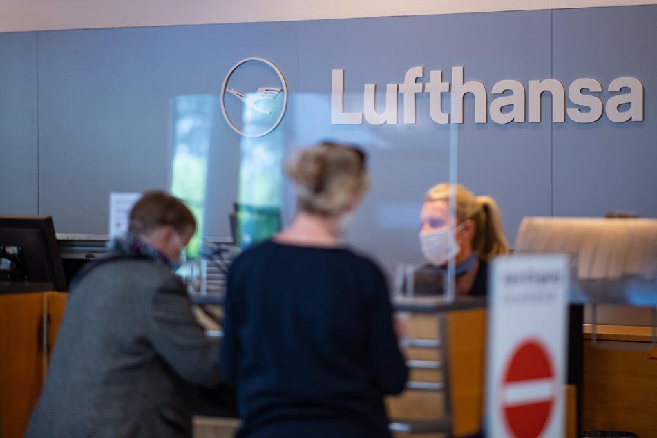 Zwei Passagiere stehen am Lufthansa Check-in Schalter am Flughafen Münster-Osnabrück.