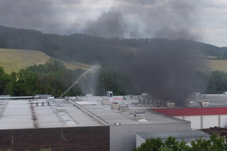 Schwarzer Rauch schwebt über der Werkshalle.