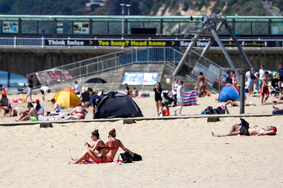 21.05.2020, Großbritannien, Bournemouth: Menschen genießen das heiße Wetter am Strand in Dorset im Süden Englands, nachdem die Regierung die Ausgangsbeschränkungen wegen der Corona-Pandemie gelockert hat.