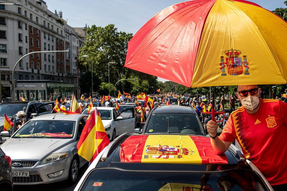 Anhänger der rechtspopulistischen Partei Vox schwenken bei einer Demonstration die Nationalflagge von Spanien.