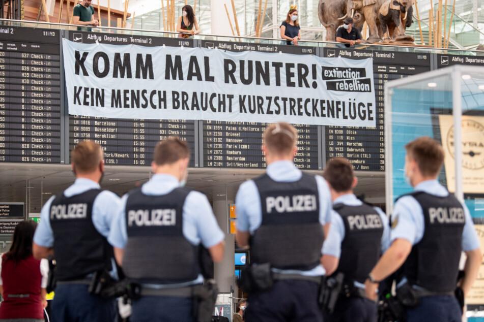 Protestaktion am Flughafen München: Aktivisten ketten sich an Kofferkulis