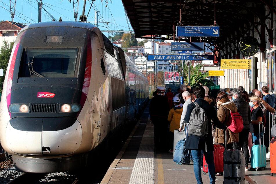Fahrgäste stehen auf einem Bahnhof und warten auf einen TGV.