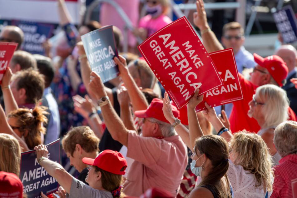 Unterstützer von US-Präsident Trump jubeln und halten Plakate hoch.