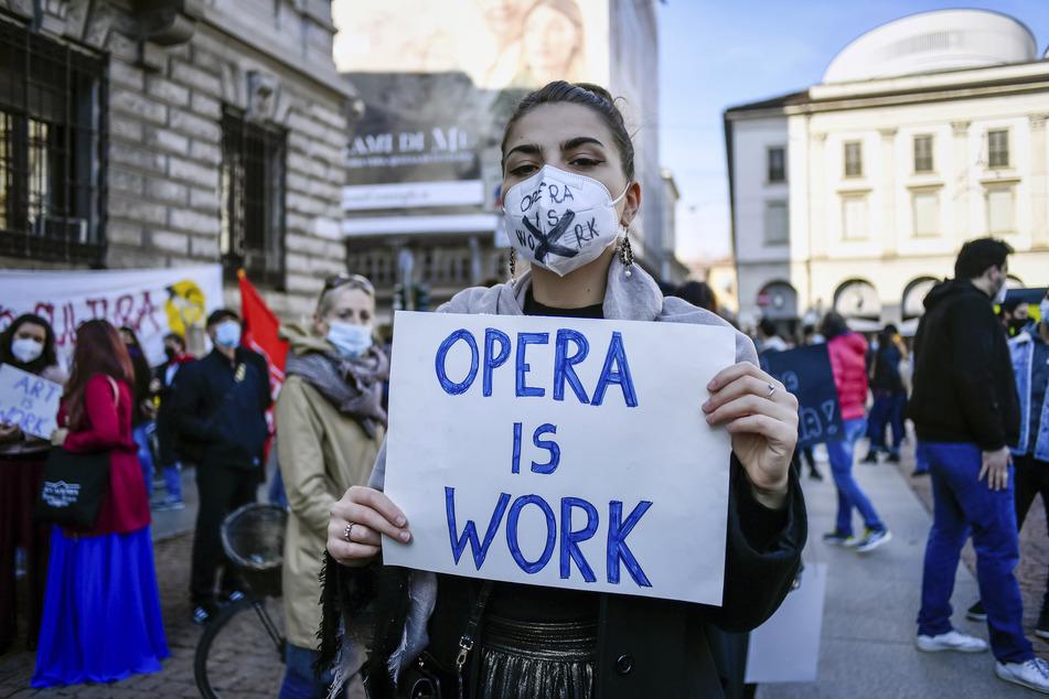 """Eine Frau hält bei einer Demonstration gegen die Maßnahmen der italienischen Regierung zur Eindämmung der Corona-Pandemie ein Schild mit der Aufschrift """"Opera is work"""" (zu deutsch: """"Oper ist Arbeit"""") in den Händen."""
