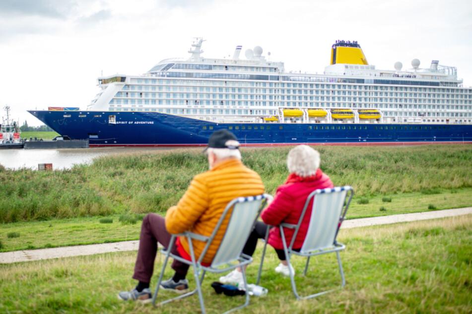 """Zwei Senioren sitzt auf dem Deich nahe des Ortsteils Dorenburg und schauen der Überführung des neuen Kreuzfahrtschiffs """"Spirit of Adventure"""" zu."""