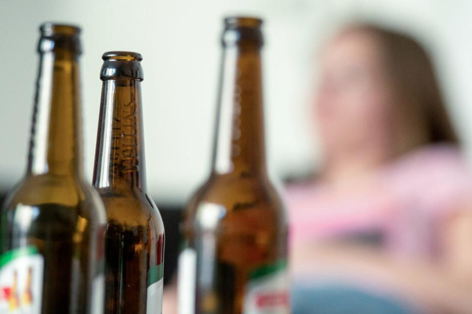 Eine junge Frau sitzt hinter leeren Bierflaschen (Symbolbild).
