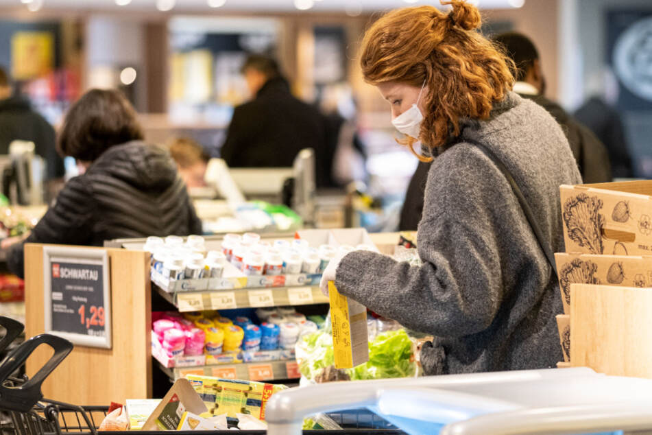 Mit einer Schutzmaske kauft eine Frau in einem EDEKA Markt ein.
