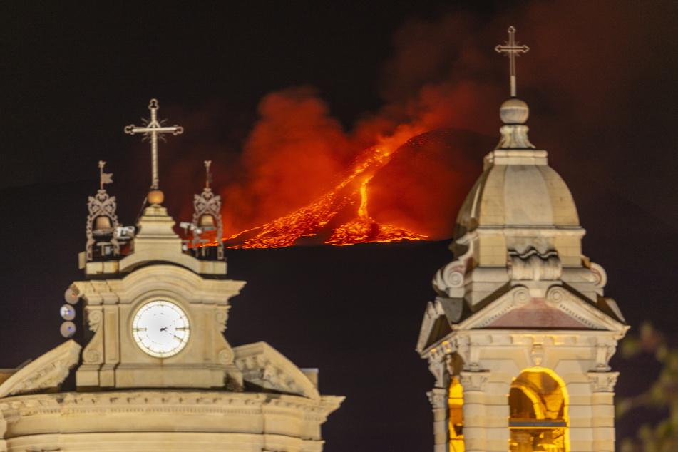 Lava bricht aus einem Krater des Ätna, Europas größtem aktiven Vulkan, hinter der Kirche Santa Maria della Guardia in Belpasso in der Nähe von Catania aus.