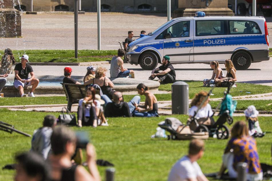 Die Polizei fährt auf dem Schlossplatz Patrouille und kontrolliert, ob die Menschen, die bei Sonnenschein die warmen Temperaturen genießen, genug Abstand zueinander halten.