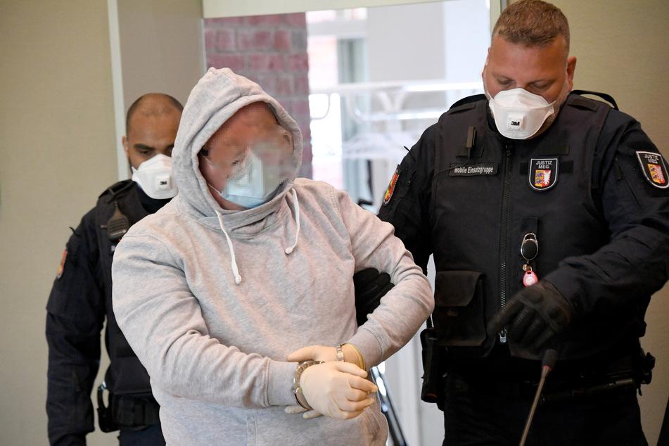 Mit Schutzbrille und Mundschutz wird der 47-Jährige Angeklagte in den Gerichtssaal geführt.