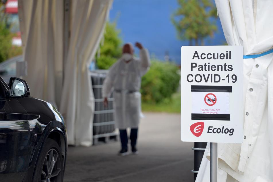 Ein Medizinischer Mitarbeiter winkt einen Autofahrer in Luxemburg in die Station, um ihn auf das Coronavirus zu testen.